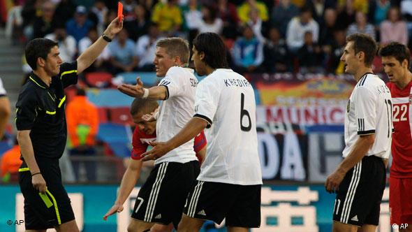 German players talk to the referee as he shows a red card