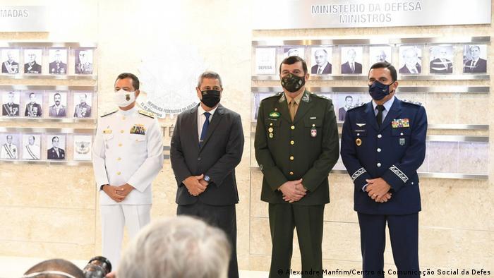 Garnier, Braga Netto, Paulo Sérgio e Baptista Junior posam para foto. Eles usam máscaras. Os comandantes estão com os trajes da Marinha, Exército e Aeronáutica. Brga Netto está de terno escuro e gravata.