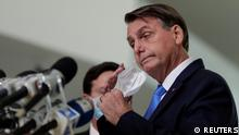 Brazil's President Jair Bolsonaro speaks to the media about the emergency financial aid by the federal government during coronavirus disease (COVID-19) crisis in Brasilia