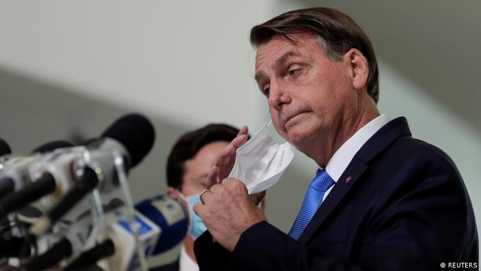 Presidente Jair Bolsonaro tira máscara de proteção diante de microfones
