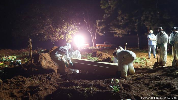 Funcionários de cemitério enterram caixão em sepultamento noturno
