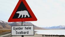 Norway, a polar bear warning sign next to a lake with snow covered mountains in the background