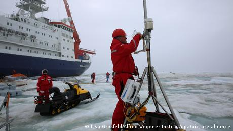 A MOSAiC expedition engineer uninstalls climate measuring sensors before returning them for analysis