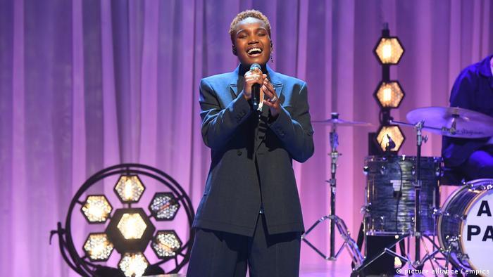 Musikerin Arlo Parks im schwarzen Anzug singt auf einer Bühne.