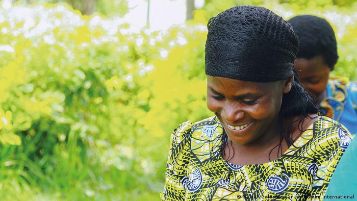 Auf dem Bild sind zwei afrikanische Frauen beim Flechten zu sehen. Sie lachen. Das Bild entstand im Rahmen eines Projektes der Organisation Women for Women International.