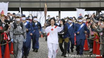 Eko Uemura trägt die olympische Fackel in Nagano