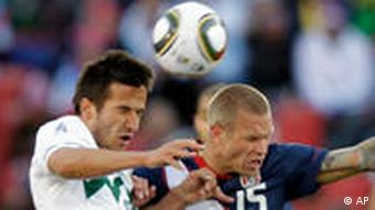 The United States' Landon Donovan, left, scores as Slovenia's Marko Suler, right, fails to block him