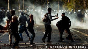Протестующие бросают палки в полицейских в брюссельсокм парке Камбрский лес