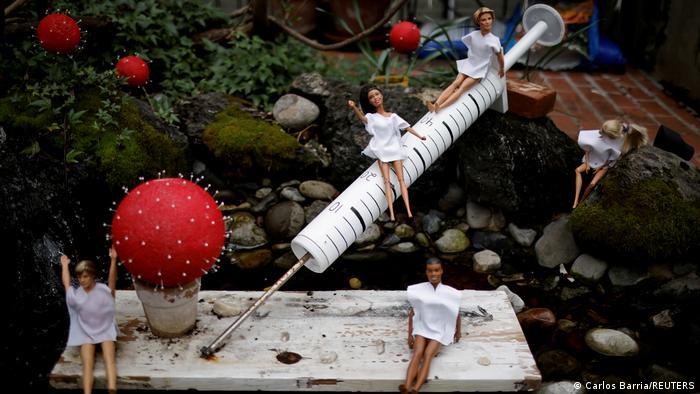 Instalación artística en un jardín de Washington: varias muñecas Barbie y muñecos Ken, vestidos de bata blanca, colocados junto a una simbólica vacuna, representando la lucha contra el coronavirus.