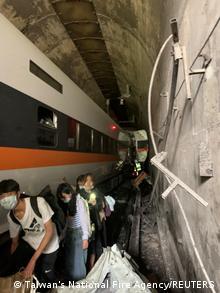 Pasajeros sobrevivientes del accidente de ferrocarril intentan salir del túnel en Hualien, Taiwán.