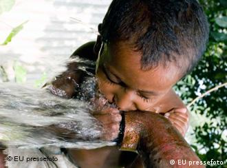 Boy drinking from water pipe in Bangladesh
