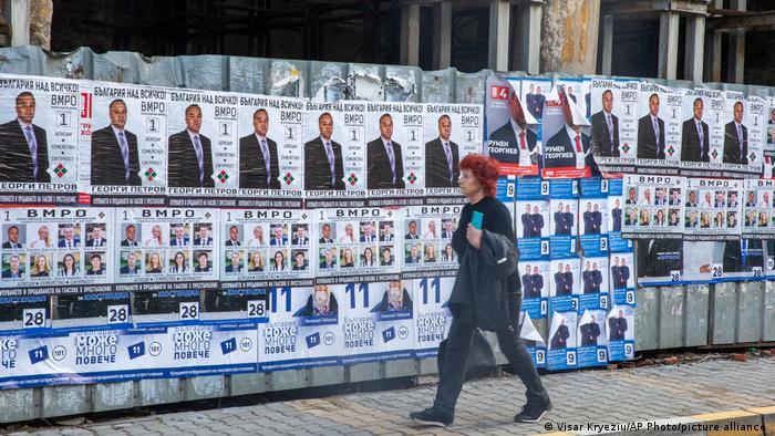 Женщина идет на фоне предвыборных плакатов на одной из улиц Кюстендила в Болгарии