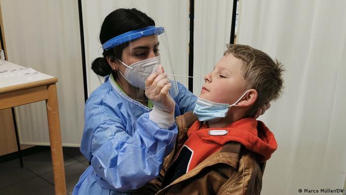Eine medizinische Fachkraft führt bei einem Kind einen Nasenabstrich durch