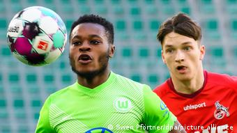 Wolfsburg's Ridle Baku controls the ball ahead of Cologne's Noah Katterbach.