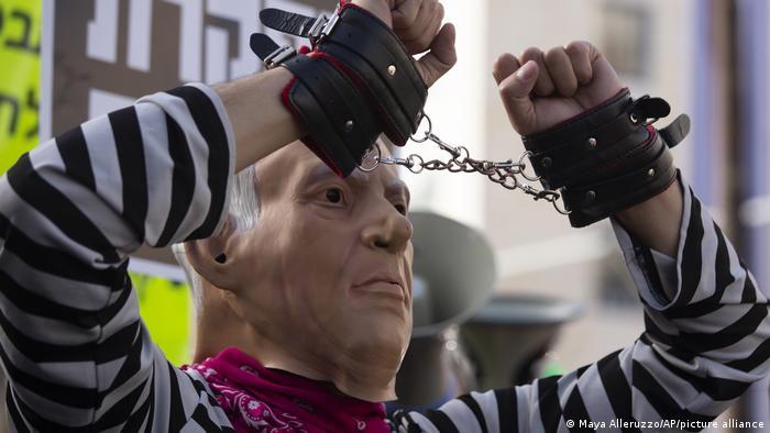 Jerusalem - ein Demonstrant mit einer Netanjahu-Maske und Handschellen