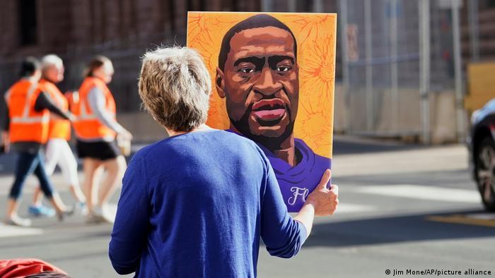 Mulher segura um retrato de George Floyd em Mineápolis