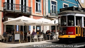 Посетители уличного кафе и трамвай в Лиссабоне