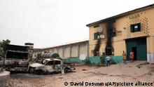 People walk past burned vehicles in front of a correctional facility in Owerri, Nigeria, on Monday, April 5, 2021. Hundreds of inmates escaped from the prison in southeastern Nigeria after a series of coordinated attacks according to government officials. (AP Photo/David Dosunmu)