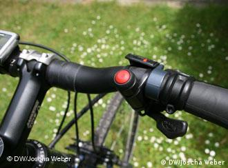 A red button on a bicycle handlebar