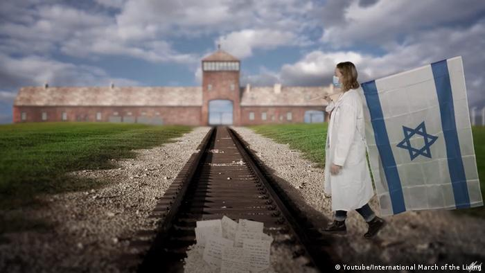 A screenshot from the 2021 virtual March of the Living promo video shows a doctor carrying the Israeli flag in front of a digitalized Auschwitz-Birkenau gate