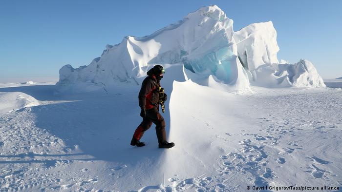 A researcher walks near ice hummocks