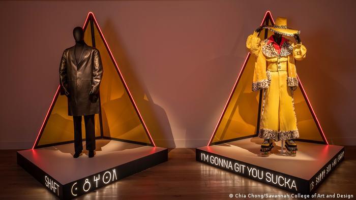 Zwei Kostüme von Ruth E. Carter stehen im Ausstellungsraum vor roten Neondreiecken aus Licht.