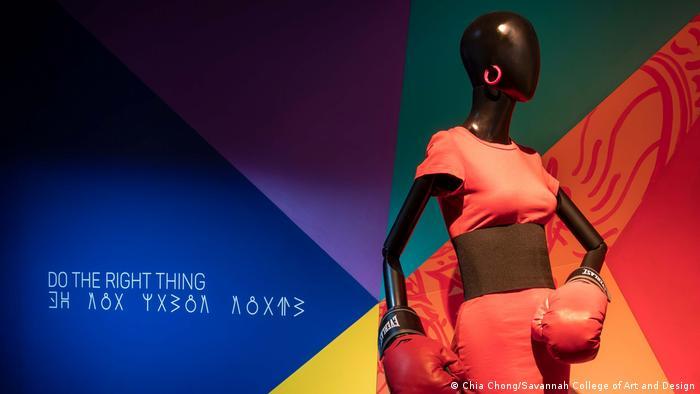 Afrofuturism in Costume Design: Ein Kostüm aus dem Film Do The Right Thing von Regisseur Spike Lee: Eine Puppe trägt ein rotes Kleid und Boxerhandschuhe