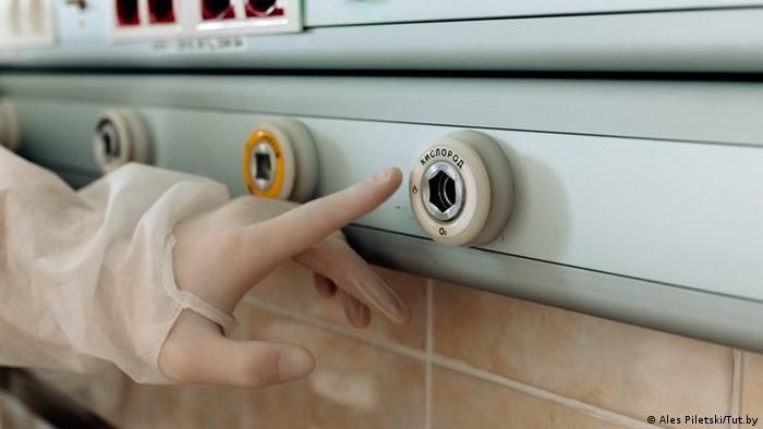 Фото Алеся Пилецкого, снимавшего в красной зоне - врач нажимает пальцем на кнопку кислород