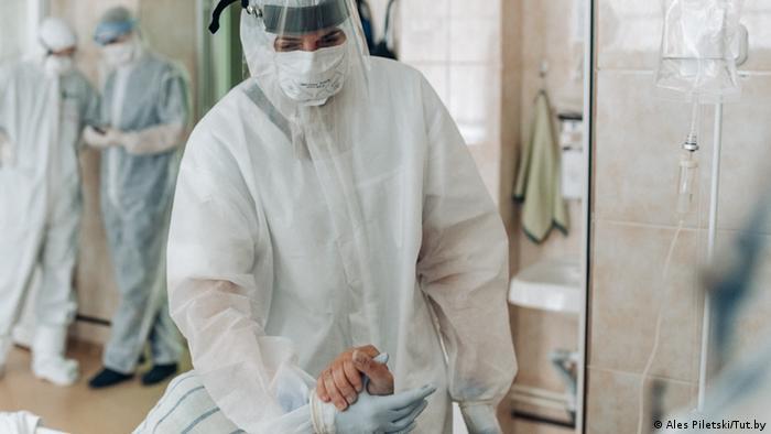 Один из снимков с закрытой выставки Машина дышит, а я - нет - врач держит за руку больного ковидом