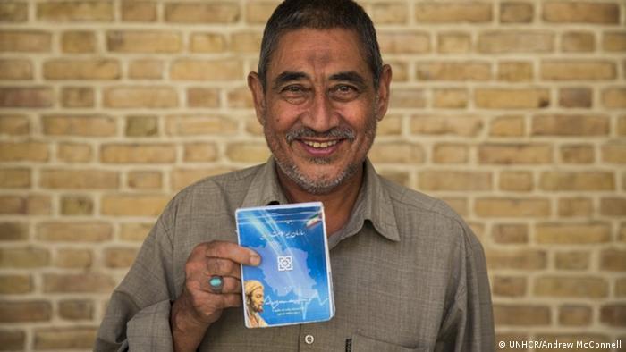 Iran Teheran   Afghanischer Flüchtling Abdulrahim Rostami mit hält Büchlein seiner Krankenversicherung
