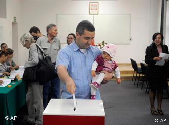 A man holds a child as he casts his ballot