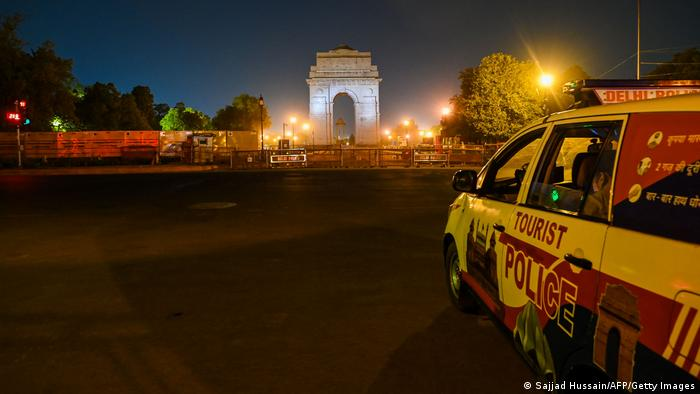 Police keep vigil at an empty street in New Delhi on April 6, 2021, as the Indian capital imposed a night curfew a day after the nation posted a record coronavirus surge, with financial hub Mumbai also introducing similar restrictions