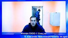 Alexei Navlany appears on a screen from inside a penal detention center.
