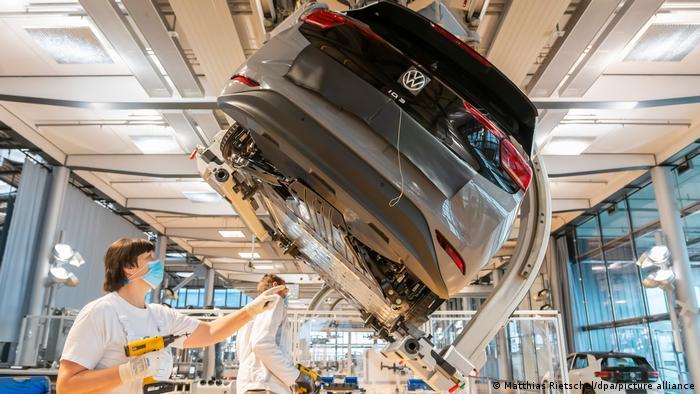 Человек в медицинской маске на производстве электромобиля Volkswagen ID.3