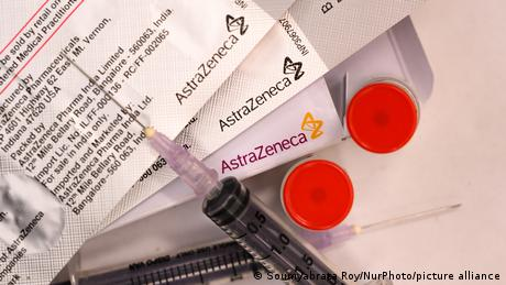 A syringe and packages of the AstraZeneca COVID vaccine are seen on a table