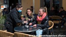 06.04.2021, Saarbrücken - Menschen werden im Außenbereich einer Gastronomie in der Innenstadt bedient. Seit dem 06.04.2021 dürfen Gastronomen im Rahmen des Saarland Modells unter Auflagen ihre Außengastronomie wieder öffnen. +++ dpa-Bildfunk +++