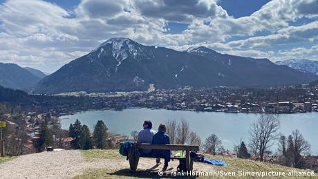 A couple sitting on a bench looking out over a lake at the foot of snow-topped mountains