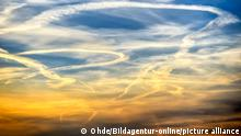 Condensation trails in the sky during sunset
