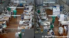 (FILES) In this file photo taken on March 26, 2021 patients affected by the COVID-19 coronavirus remain at a field hospital set up at a sports gym, in Santo Andre, Sao Paulo state, Brazil. - Latin America and the Caribbean passed on April 2, 2021 the 25 million mark for recorded coronavirus cases as a surge in infections saw countries place restrictions on travel and movement while vaccine campaigns catch up. (Photo by Miguel SCHINCARIOL / AFP)