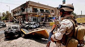 An Iraqi Army soldier stands guard at the site of a car bomb attack in Baghdad, Iraq