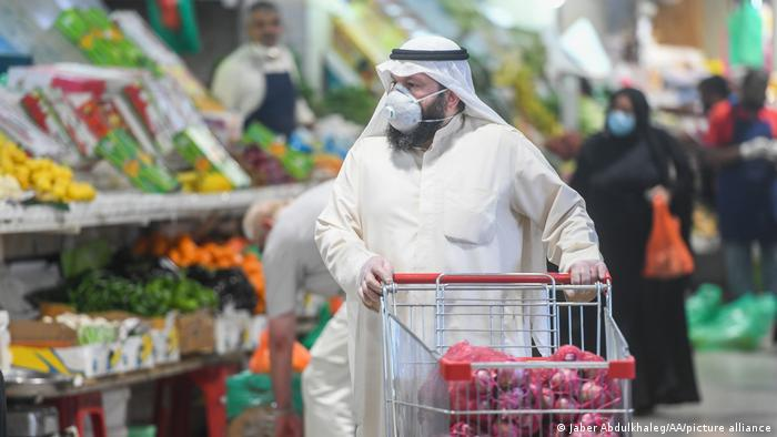 A man pushing a shopping cart in a supermarket in Kuwait with large bags of red onions