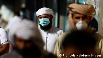 Прохожие в масках на одной из улиц Дубая