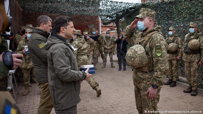 Der ukrainische Präsident Selenskyj ehrt an der Front einen Soldaten