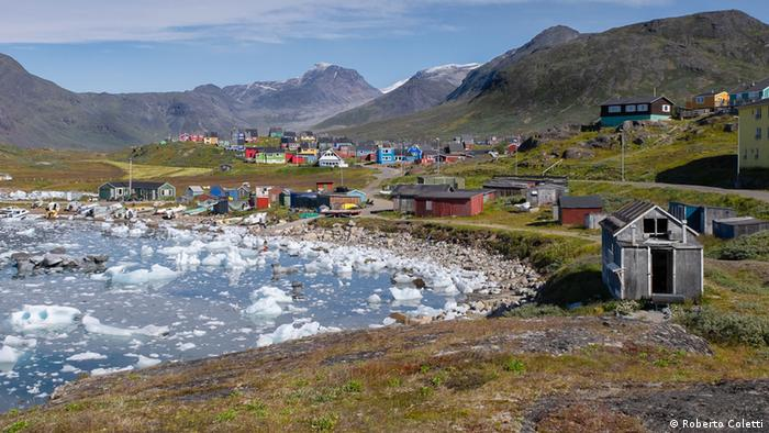 Kleine Häuser in einer hügeligen Landschaft am Rande eines eisigen Fjordes in Grönland