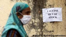 Woman walks past a sign saying vaccine out of stock in Mumbai