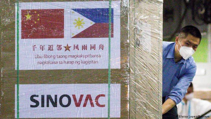 Чоловік у масці розвантажує вакцину Sinovac Biotech (лютий 2021 року)