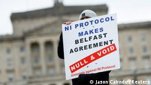 A man holds a sign, as pro-British unionists demonstrate near Parliament buildings, amid nightly outbreaks of street violence in the region that have left dozens of police officers injured, in Belfast, Northern Ireland, April 8, 2021. REUTERS/Jason Cairnduff