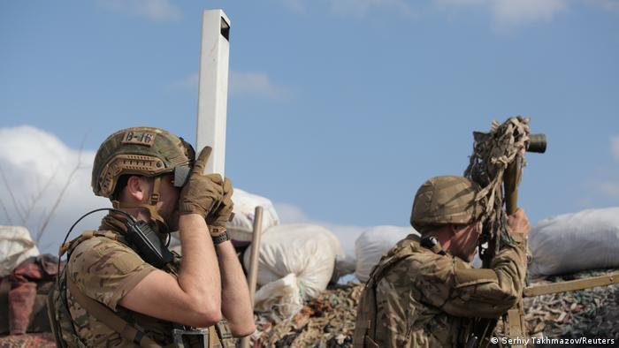 Service members of the Ukrainian armed forces observe the area from their fighting positions