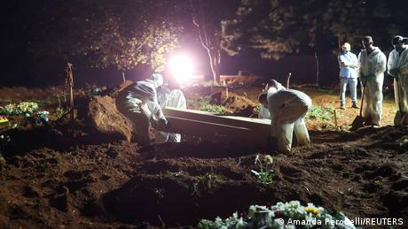 Gravediggers in protective suits carry out nigh-time burial of COVID victim in Sao Paulo