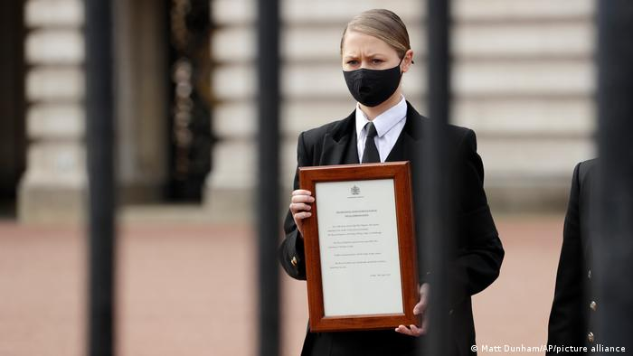 Buckingham Palace staff member carries framed announcement of Philip's death to the gate